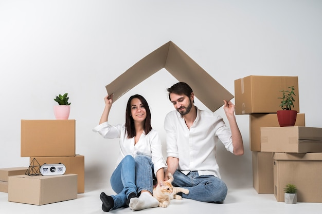 Cute young family posing next to cardboard boxes Premium Photo