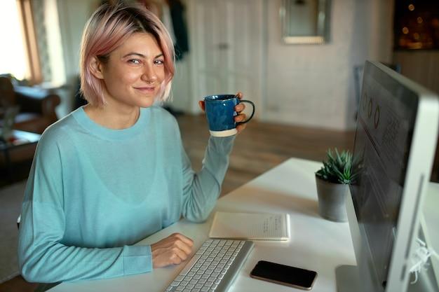 Carino giovane femmina graphic designer che lavora sul contenuto visivo per il sito web, utilizzando il computer desktop, avendo tè, sorridendo alla telecamera Foto Gratuite