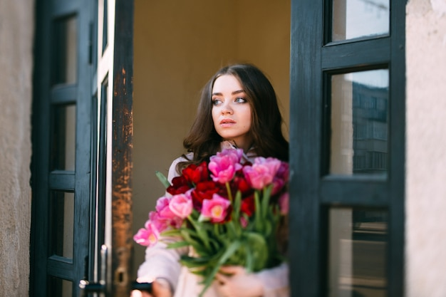 Cute young female with flowers opening door and looking out Premium Photo