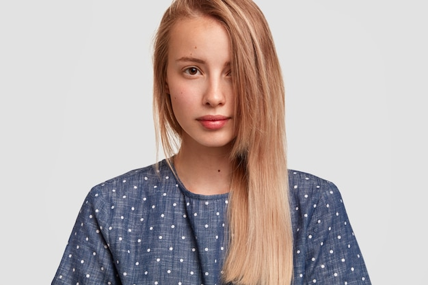 Cute young female with long hair combed on one side, looks seriously, shows her healthy perfect skin, dressed in polka dot blouse, poses against white wall. people, beauty, lifestyle concept Free Photo