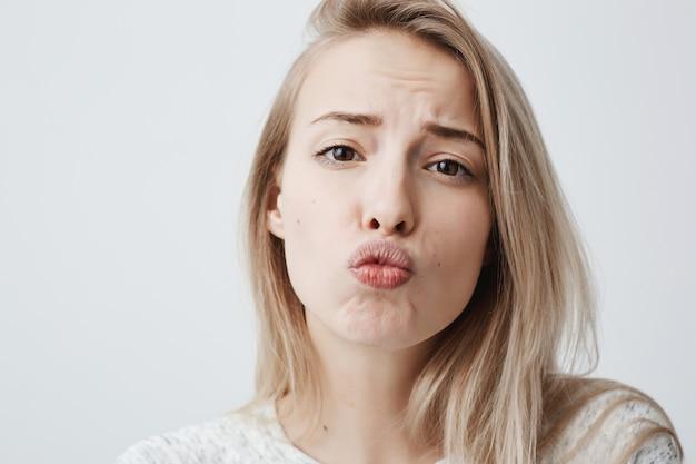 薄い肌、長いブロンドの髪、カジュアルなセーターを着ている、唇を丸める、コケットに見えるかわいい若い女性 無料写真
