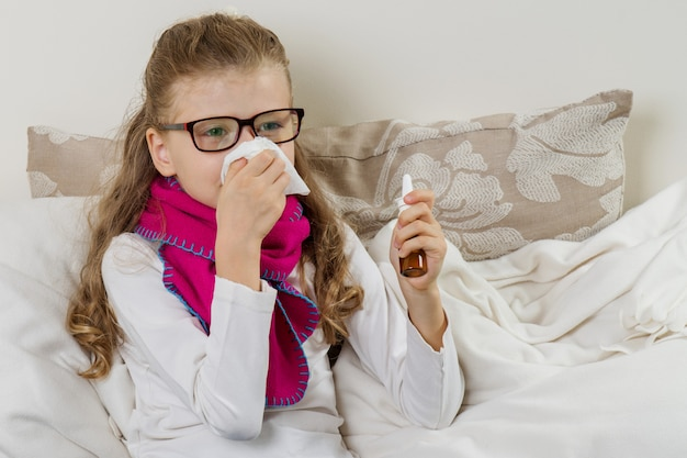 Cute young girl child sneezing in a tissue blowing his runny nose Premium Photo