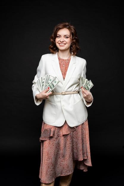 La ragazza carina mostra un sacco di soldi nelle mani, immagine isolata su uno spazio nero Foto Gratuite