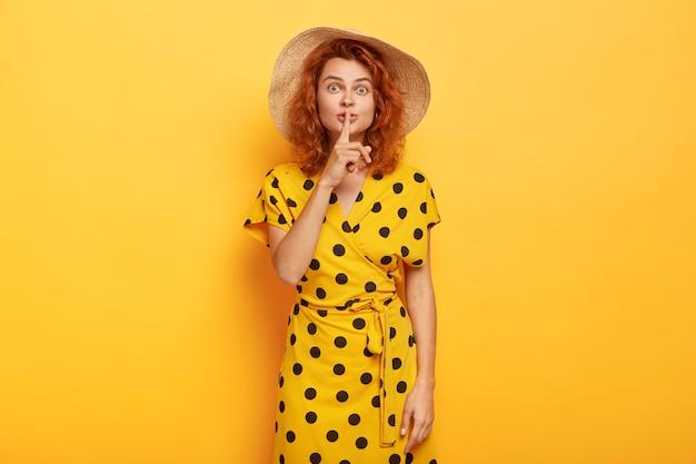 Симпатичная молодая девушка с удивленным выражением лица демонстрирует жестикуляцию, держит указательный палец над ртом, у нее рыжие волнистые волосы, она одета в модное платье в горошек, рассказывает секрет, изолирована на желтой стене Бесплатные Фотографии