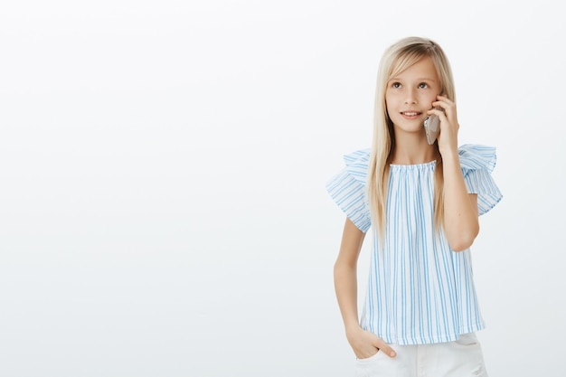엄마가 대답하는 동안 전화를 기다리는 귀여운 어린 소녀. 세련 된 파란색 블라우스에 꿈꾸는 행복 금발 딸의 초상화, 주머니에 손을 잡고, 찾고 스마트 폰 이야기 무료 사진