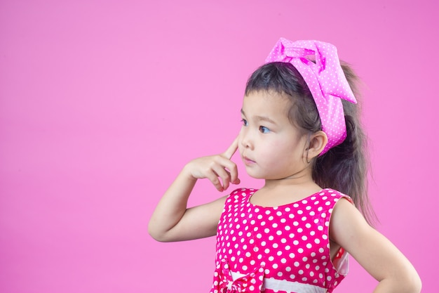 Cute young girl wearing a red striped shirt, tied a pink bow on the head and pink . Free Photo