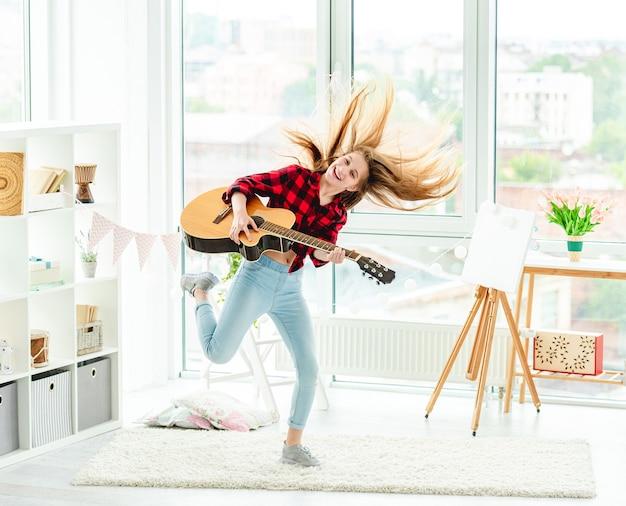 自宅で高いジャンプでギターを持つかわいい若い女の子 Premium写真