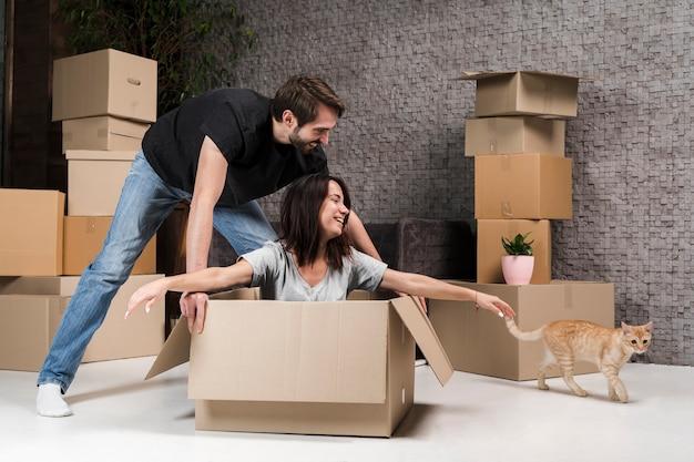 Симпатичный молодой мужчина и женщина празднуют переезд Premium Фотографии