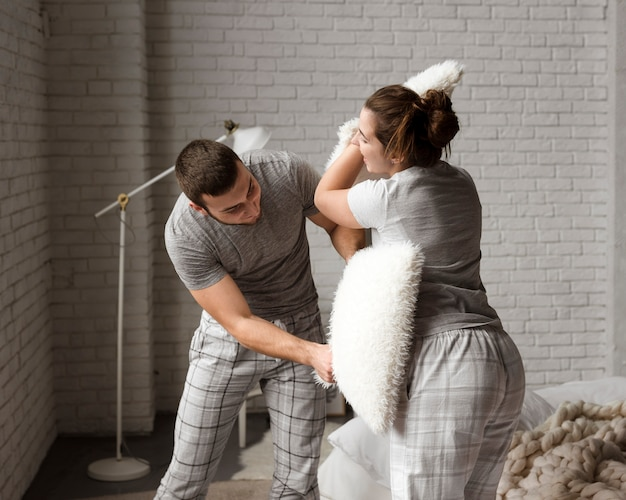 Cute young man and woman pillow fighting indoors Free Photo
