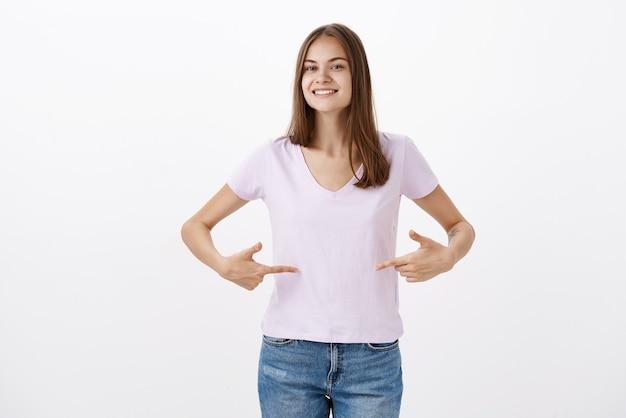 Carina giovane sportiva che dà consigli su come rimanere in forma sorridendo gioiosamente guardando amichevole indicando t-shirt o pancia in piedi deliziata e soddisfatta con sguardo felice oltre il muro grigio Foto Gratuite
