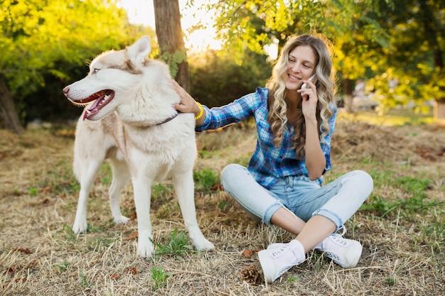 日当たりの良い夏の日に公園で犬ハスキー犬と遊ぶかわいい若いスタイリッシュなかなり笑顔幸せな金髪女 無料写真