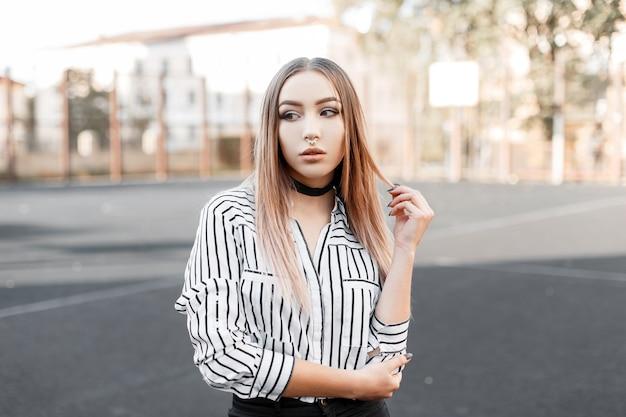 黒のベルベットのネックレスと黒のジーンズでファッショナブルなストライプのシャツに鼻ピアスのかわいい若いティーンエイジャーの女性は、春の晴れた日に屋外に立っています Premium写真
