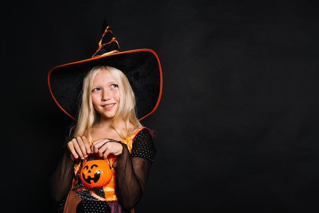 Cute young witch in hat Free Photo