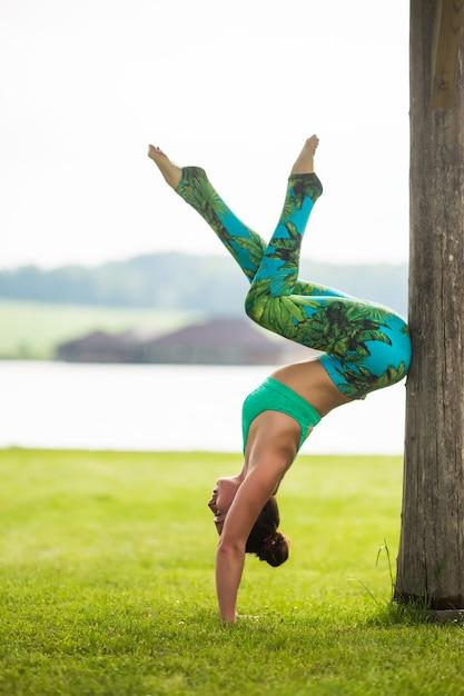 Giovane donna sveglia che fa esercizi di handstand nel parco verde Foto Gratuite