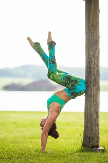 Милая молодая женщина делает упражнения стойки на руках в зеленом парке Бесплатные Фотографии