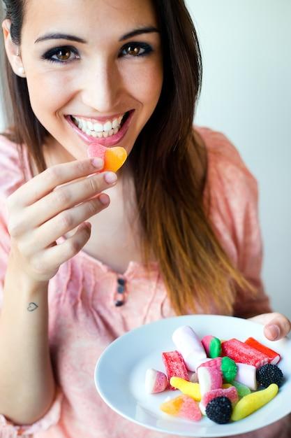 かわいい若い女性は、新鮮な笑顔でゼリーのキャンディーを食べる Premium写真