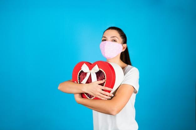 Милая молодая женщина в защитной маске, обнимая подарочную коробку валентинок в форме красного сердца на синем. Premium Фотографии