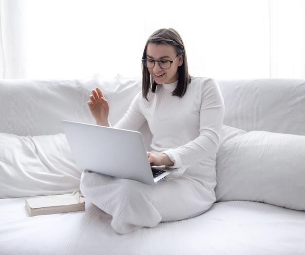 Una giovane donna carina è seduta a casa su un divano bianco in un abito bianco e lavora su un laptop. Foto Gratuite