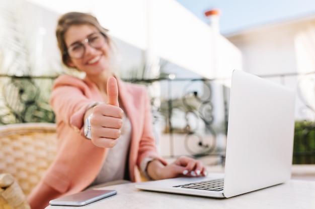 Carina giovane donna, studente, donna d'affari che mostra i pollici in su, ben fatto, seduto in un caffè all'aperto sulla terrazza con il computer portatile. indossare abiti rosa eleganti. Foto Gratuite
