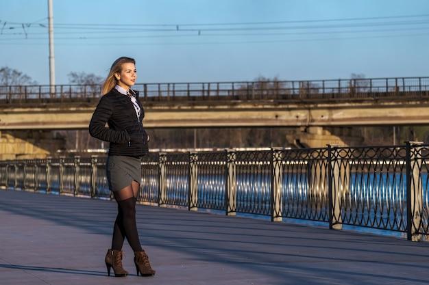 Милая молодая женщина, ходить по набережной в солнечный день. Premium Фотографии