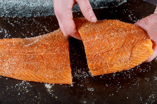 The cuted salmon fillets in hands on black board. Premium Photo