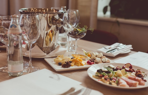 Cutlery, appetizers, spittoon and glasses on the wooden table in the restaurant Premium Photo