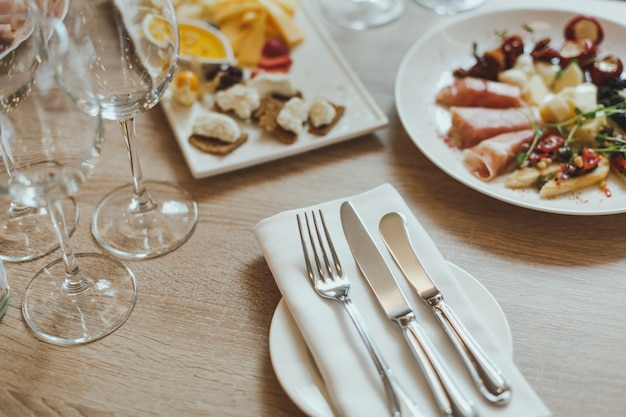 Cutlery, appetizers and wine glasses on the wooden table in the restaurant. Premium Photo
