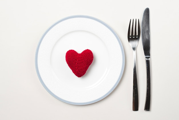 Cutlery near plate with heart Free Photo