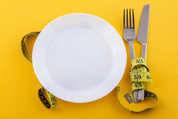 Cutlery and a white plate with measuring tape on a yellow, the concept of weight loss and diet Free Photo