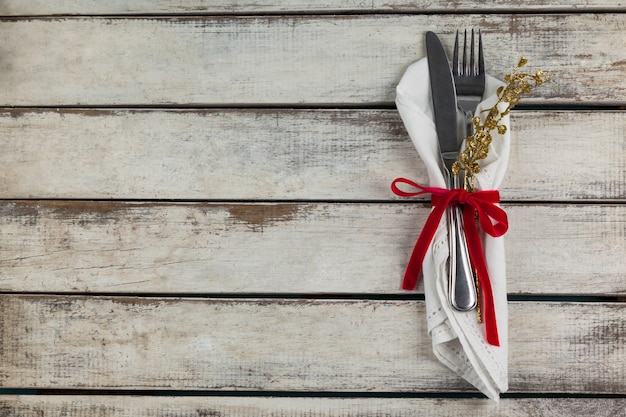 Cutlery wrapped with christmas motif on a wooden table Free Photo