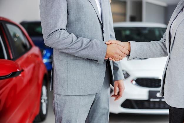カーサロンに立っている間、買い手と握手する車の売り手の切り抜き写真。 Premium写真