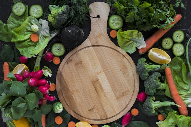 Cutting board amidst vegetables Free Photo