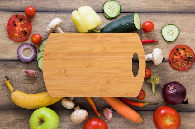 Cutting board surrounded by different fruits and vegetables Free Photo