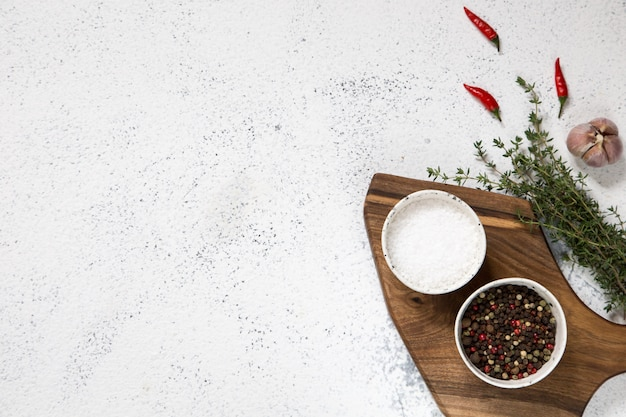 Cutting board with herbs on white concrete Premium Photo