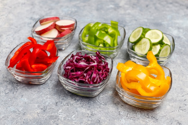 Cutting board with slices of colorful bell peppers on light surface. sliced sweet peppers in different colors, vegetable salad ingredient, cooking healthy food, top view Free Photo