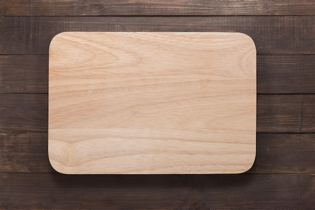 Cutting board on the wooden background. top view Premium Photo
