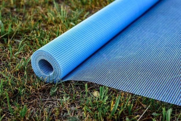 Резка фасадной сетки по траве. Premium Фотографии
