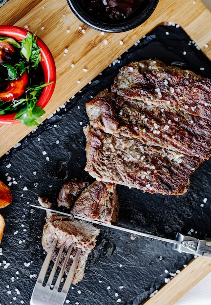 Cutting steak with knife and fork. Free Photo