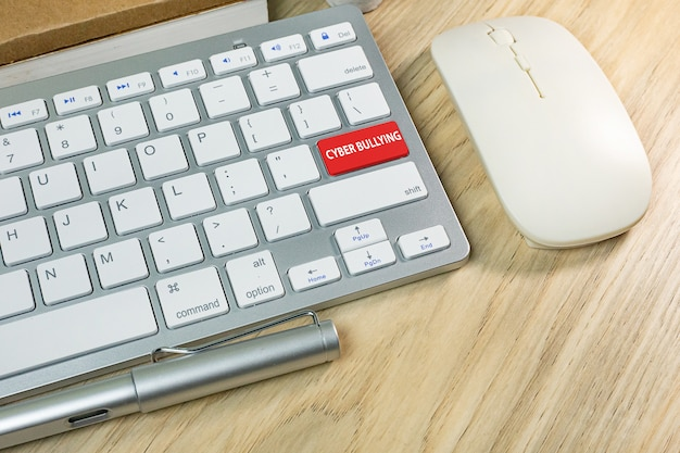 Cyber bullying red button on silver keyboard . Premium Photo