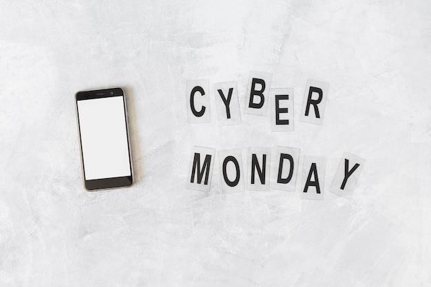 Смартфон с надписью cyber monday на столе Бесплатные Фотографии
