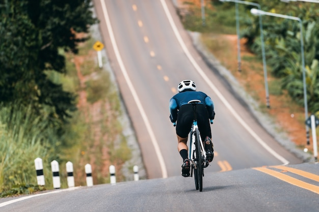 Cyclist adjusting posture to reduce air resistance. in the bike down the hill. Premium Photo