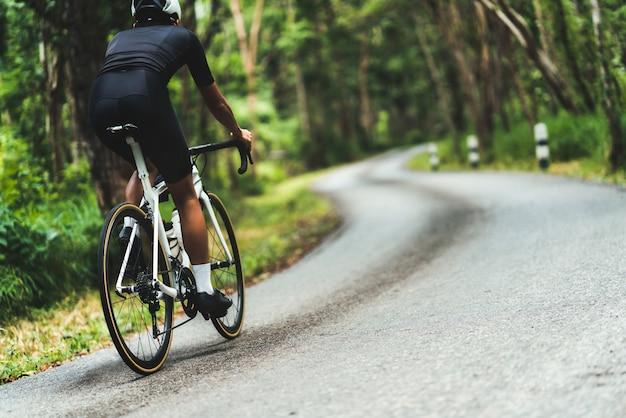 サイクリスト彼は森の中を登りながら上り坂をサイクリングしていました。 Premium写真