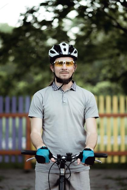 스포츠웨어와 헬멧의 사이클리스트는 공원의 도로에 서서 정면을 바라보고 있습니다. 프리미엄 사진