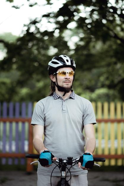 스포츠웨어와 헬멧을 착용 한 사이클리스트가 공원의 길에 서서 옆을 바라 봅니다. 프리미엄 사진