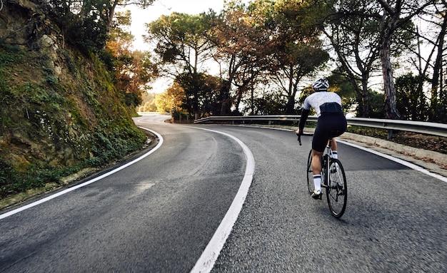 Uomo ciclista in sella a una bicicletta sulla strada Foto Gratuite