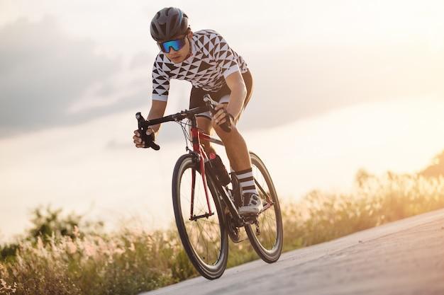 Велосипедист крутил педали на гоночном велосипеде на открытом воздухе Premium Фотографии