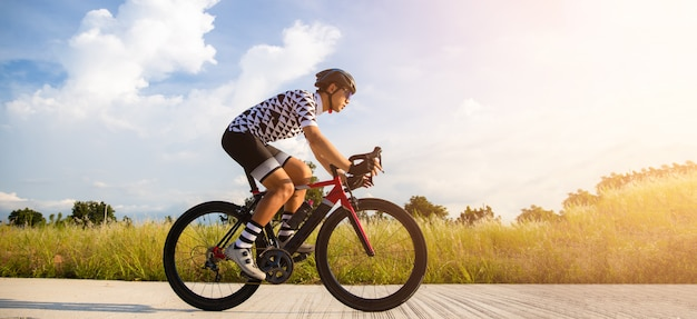 Cyclist pedaling on a racing bike outdoors Premium Photo