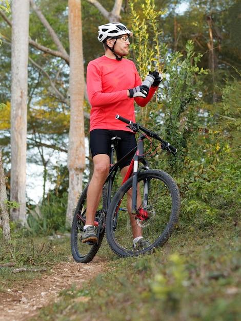 熱帯林で休息し、等張性の飲み物を飲むサイクリストは、自転車用ヘルメットと赤いサイクリングジャージを着ています。 Premium写真