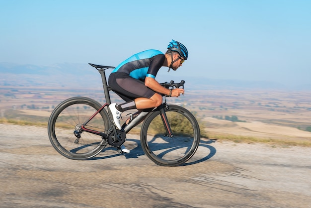 Cyclist riding the bike in the road descending the hill Premium Photo