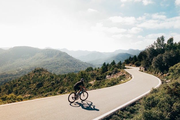 Cyclist riding a bike at sunset in a mountain road Free Photo